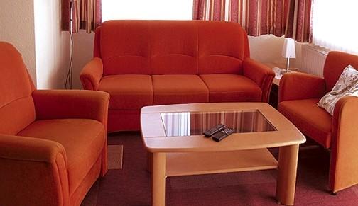 Sitzgarnitur im Wohnraum mit Fernseher.